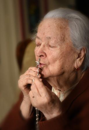Oude vrouw bidden met zilver rozenkrans met kruis in haar handen op home.The grijsharige zieke vrouw bellen naar God Stockfoto