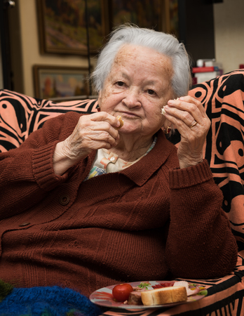Old woman eating at home photo
