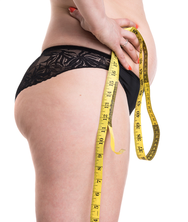 減量、ダイエット、痩身、サイズ概念。白地にメジャー テープで下着で若いプラスのサイズの女性