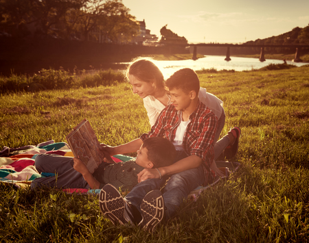 Summer, childhood, leisure concept. Children sitting on the grass and reading book in the park. Sunny summer day