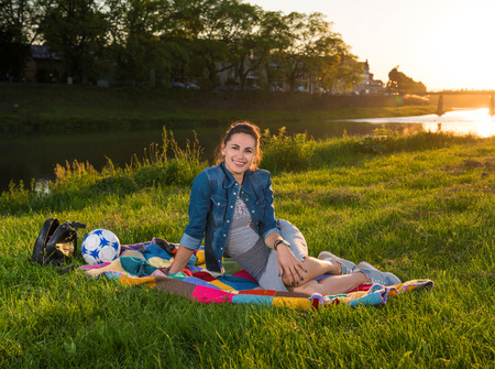 Summer,  leisure concept. Happy smiling woman resting on the grass outdoors. Summer sunny say