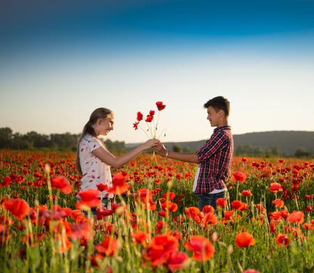 Teen boy and girl posing on the poppy field at sunset. Summer sunny day photo