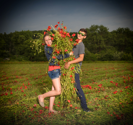 Summer, childhood, leisure concept. Teen boy and girl posing on the poppy field at sunset photo