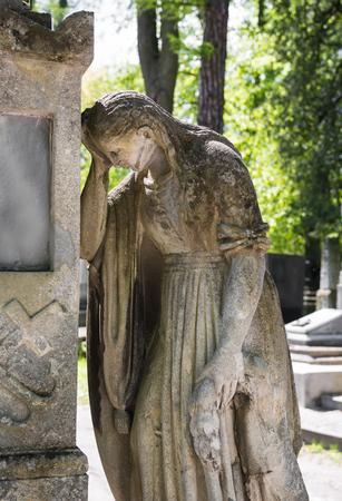 LVIV, UKRAINE - Apr 27, 2016: Old statue on grave in the Lychakivskyj cemetery in Lviv, Ukraine.