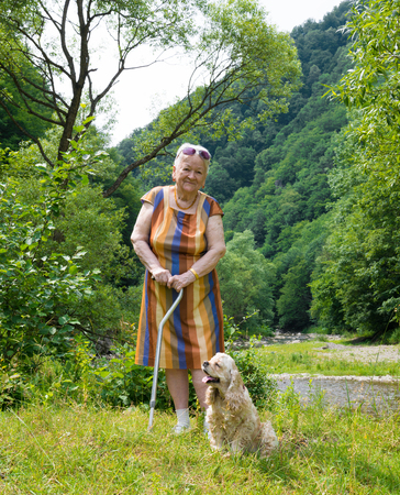 Old woman walking in summer park with a dog. Sunny day photo