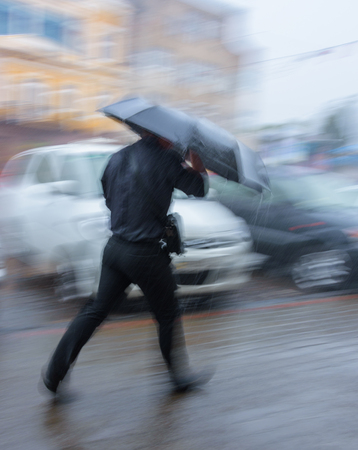 Man walking down the street in rainy day in motion blur