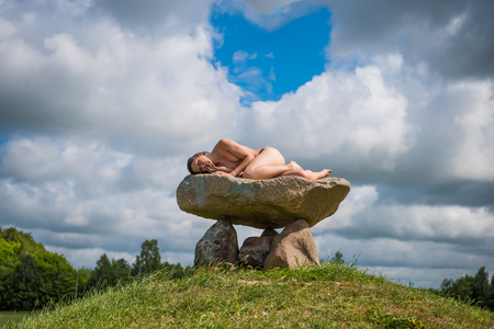 Young nude woman enjoying summer time outdoors in hot sunny day. Sexy brunette posing on a huge stone Stock Photo