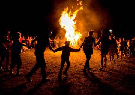 outdoor fireplace: VOROCHEVO, UKRAINE - JULY 16, 2017: Lemko Vatra festival in Vorochevo, Ukraine. People resting near big bonfire outdoor at night Editorial