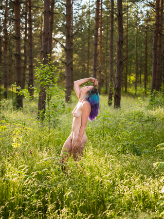 Romantic image of young naked woman posing outdoors. Enjoying summer time 스톡 콘텐츠