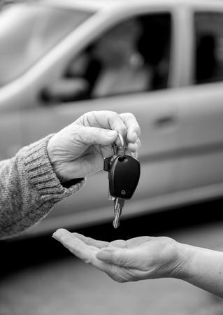 selling service: Woman giving car keys to another woman opposite car