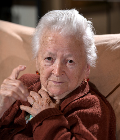 Old gray-haired woman in angry gesture posing at home