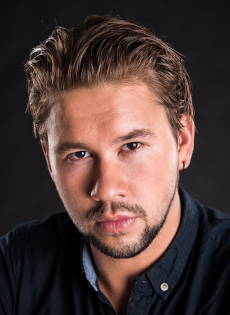 Portrait of handsome bearded man with stylish hair.  Smart serious young man posing on a black background
