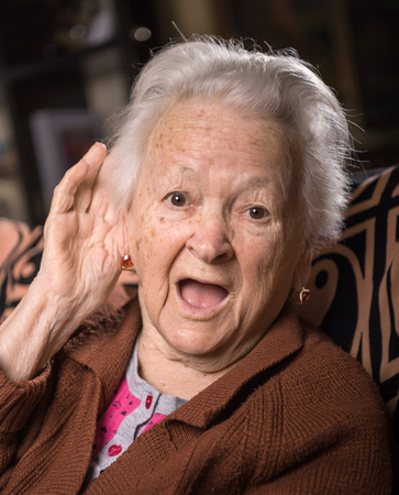 Portrait of old woman putting hand to her ear. Bad hearing, hearing loss , hard of hearing Stock Photo