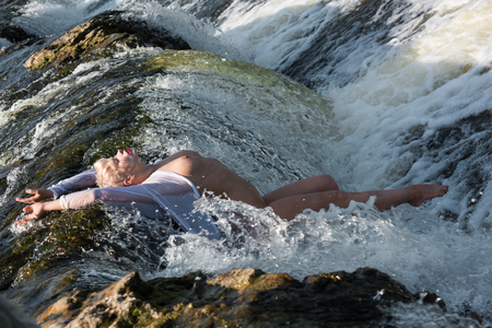 Beautiful young seminude woman in white shirt enjoying summertime in the waterfall. Enjoying and relaxing in the water. Summer sunny day Stock Photo