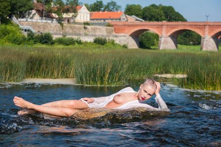 滝で夏を楽しむ白いシャツの美しい若い seminude 女性。水の中で楽しんでリラックスしています。夏の晴れた日