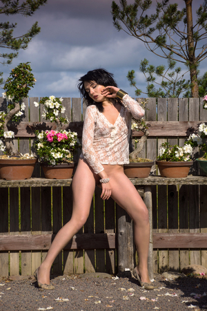 Romantic image of young seminude brunette woman posing outdoors. Enjoying summer time in the garden