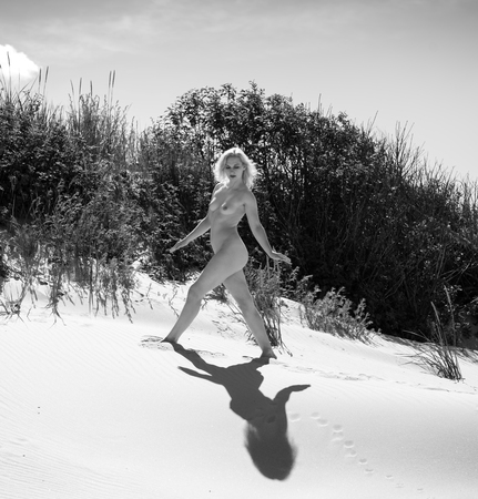 Young nude woman posing on a sandy beach. Sexy blondel enjoying hot summer day outdoors Banque d'images