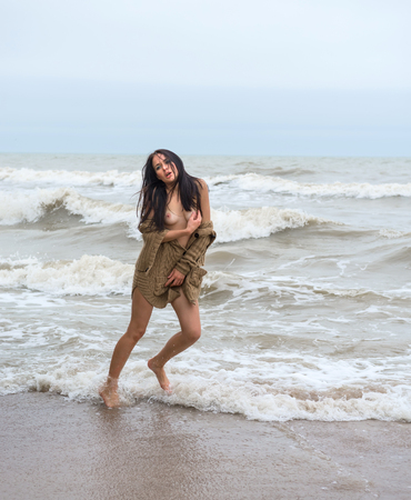 Beautiful young seminude woman in the cold sea waves
