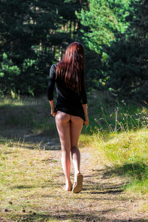 Young seminude woman in black blouse posing on nature background. Enjoying summer time in the forest