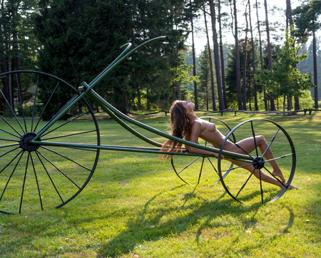 Young nude woman enjoying summer time outdoors. Sexy brunette posing near decorative bike in hot sunny day Standard-Bild