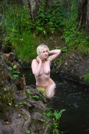 Beautiful blonde young nude woman enjoying summertime in the river Archivio Fotografico
