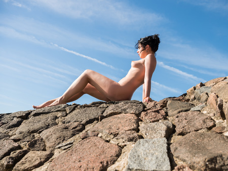 Young nude woman enjoying summer time outdoors in hot sunny day. Sexy brunette posing on stone