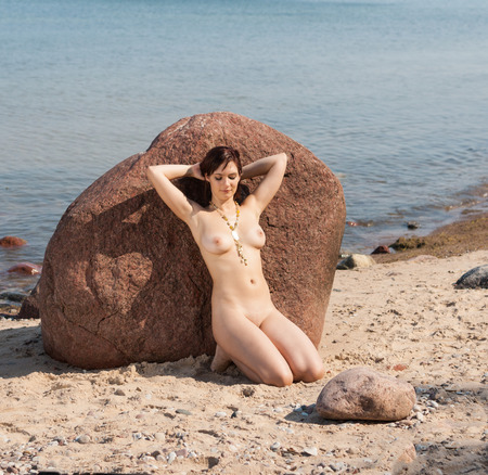 Young nude woman lying on stone against the sea background. Enjoying sunny day and summer time 스톡 콘텐츠