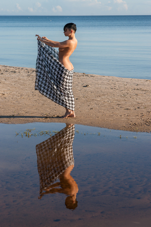 Young naked woman posing at the beach with fabric. Enjoying summer time  and hot day near the sea Stockfoto