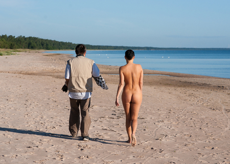 Photographer and young nude model at the beach Foto de archivo