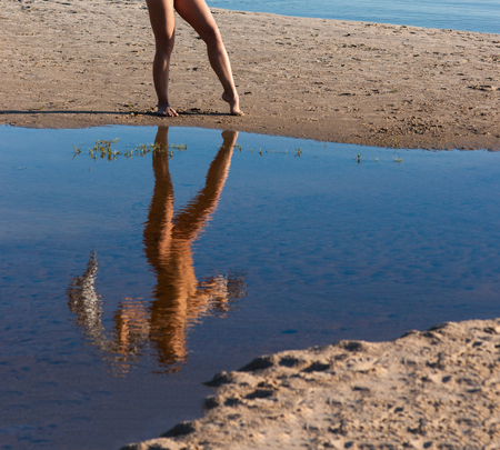 Young naked woman posing at the beach. Reflection of nude brunette in the water 免版税图像