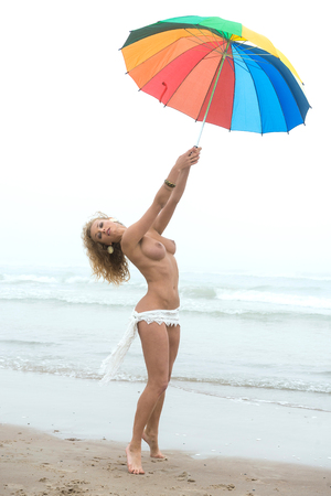 Beautiful nude woman with colorful umbrella posing on sandya beach in foggy day