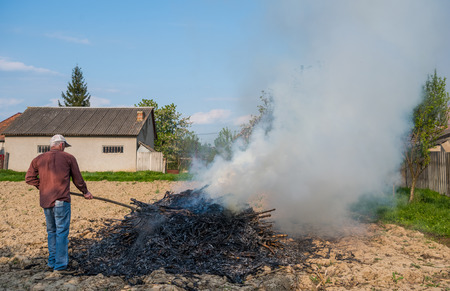 Agricultural concept. Work in the garden. Farmer burning dried branches. Spring time