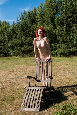 Beautiful young naked woman posing near wooden chair. Enjoying summer hot day Stock Photo