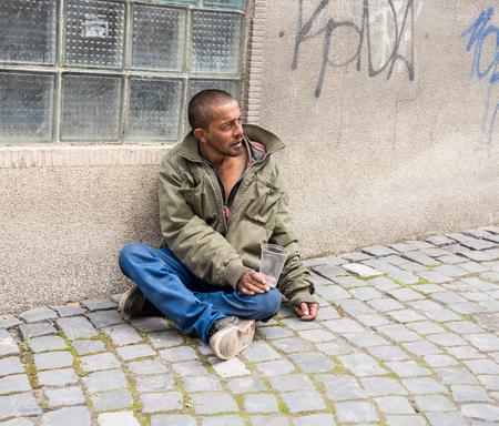 Homeless man on the street of the city. Senior beggar