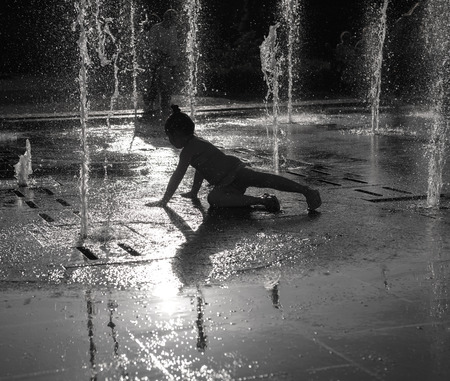 Happy girl having fun between water jets in fountain. Summer time