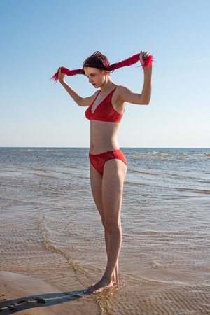 Beautiful redhead young woman in red transparent swimsuit posing at the beach