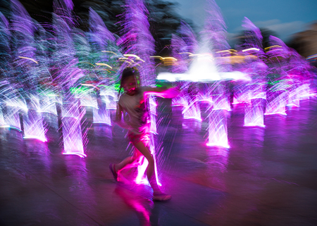Happy children playing in a water fountain in evening lights in motion blur