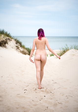 Young nude woman posing on a sandy beach. Sexy female enjoying hot summer day outdoors Standard-Bild