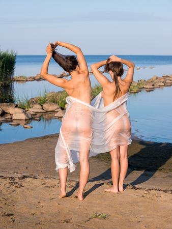 Two young nude women wrapped in white shawl posing on the beach. Sexy naked brunettes enjoying summer time outdoors
