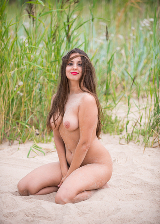 Romantic image of young naked woman posing outdoors. Enjoying summer time in hot day