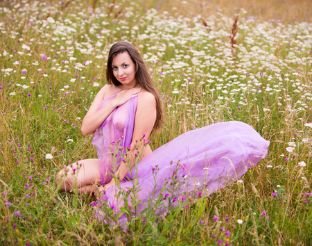 Young nude woman in pink shawl posing on the field. Sexy blonde enjoying nature and summer time outdoors Banque d'images