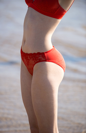 Beautiful young woman in red transparent swimsuit posing at the beach Stock Photo
