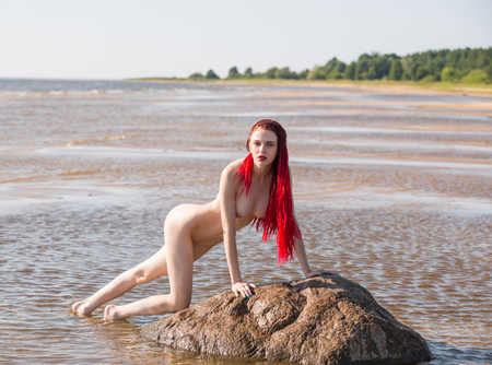 Beautiful naked young woman posing in the sea. Sexy nude redhead enjoying summertime at the beach Standard-Bild