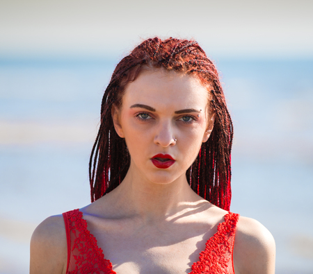 Portrait of beautiful redhead young woman in red transparent swimsuit posing at the beach