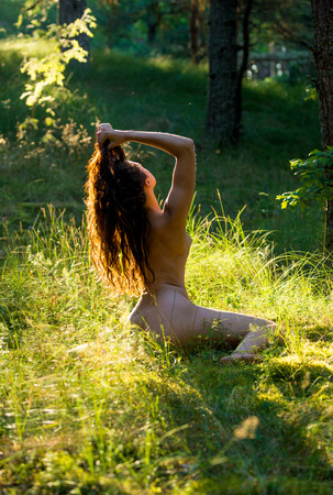 Romantic image of young naked woman posing outdoors at sunset. Enjoying summer in evening rays of light
