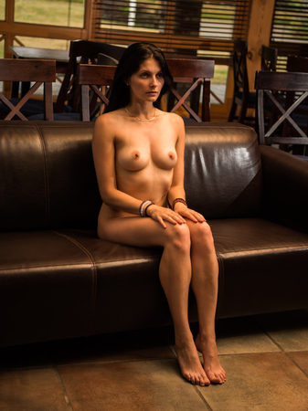 Gorgeous naked brunette posing indoors. Sexy nude woman relaxing on sofa