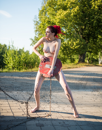 Nude beautiful woman holding STOP road sign and covering herself outdoors. Sexy redhead posing in hot summer day