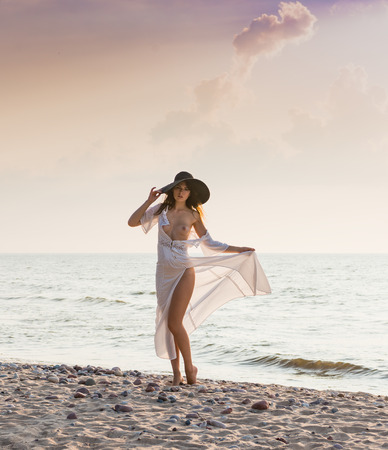 Beautiful young naked woman in white dress posing at the beach. Enjoying summer time