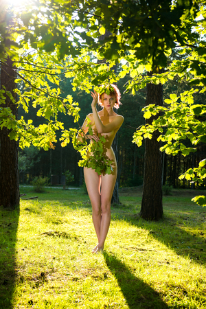 Young nude woman posing near the tree. Naked woman sunbathing and enjoying nature and summer time. Relaxing on sunny summer day. Sexy naked redhead Stock Photo