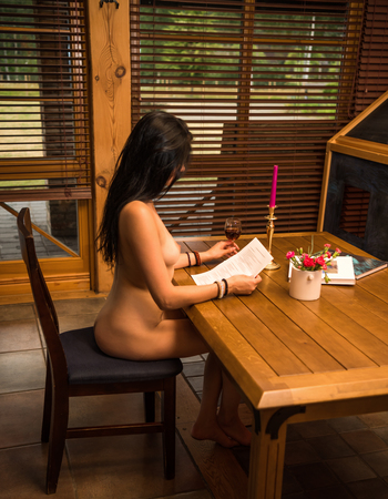 Gorgeous naked brunette posing indoors. Sexy nude sitting at the table and reading a letter. Holding glass of wine